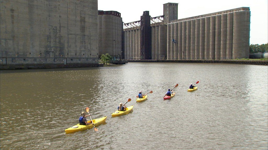 Kayakers paddle past old grain silos along the Buffalo River. Photo by Eileen Elibol.