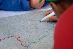 An individual drawing on a map.