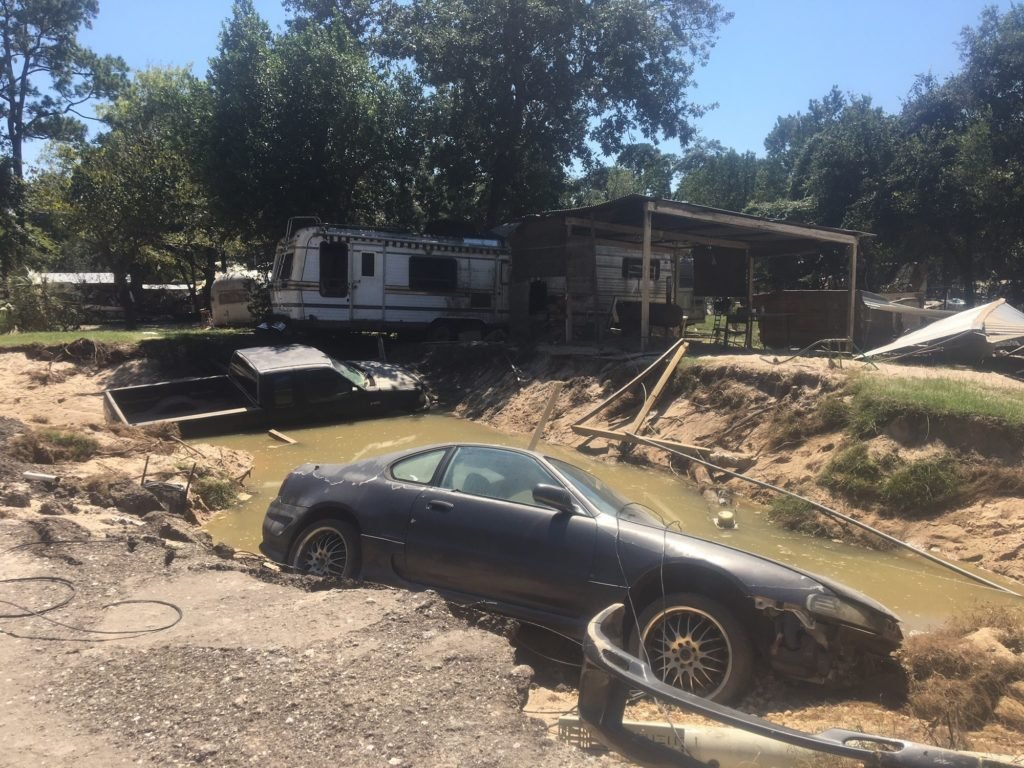 The wreckage left behind by the hurricane included cars semi-submerged in a sinkhole formed by the floods, directly next to a Superfund site.