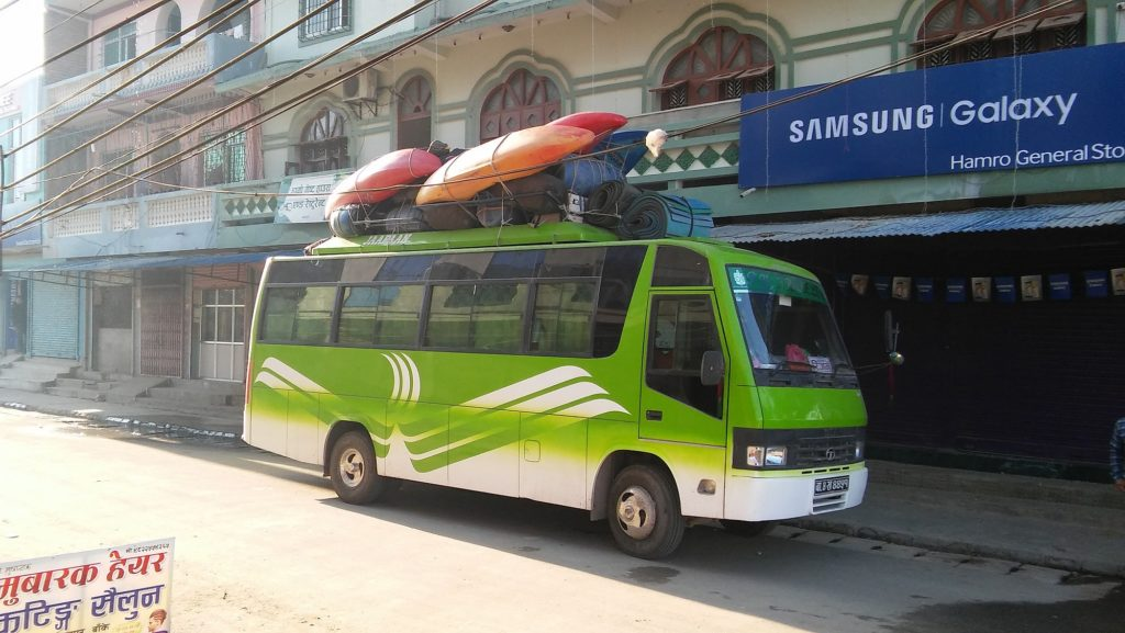 Green charter bus with kayaks on top.