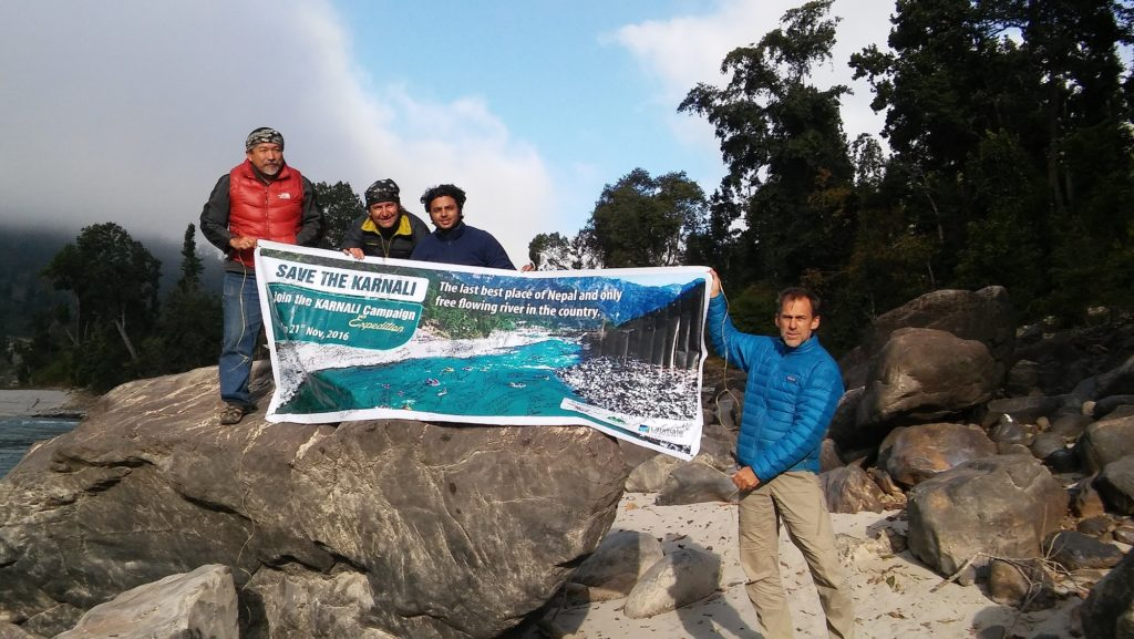 "Four men holding a sign on top of a rock that says ""Save the Karnali"""