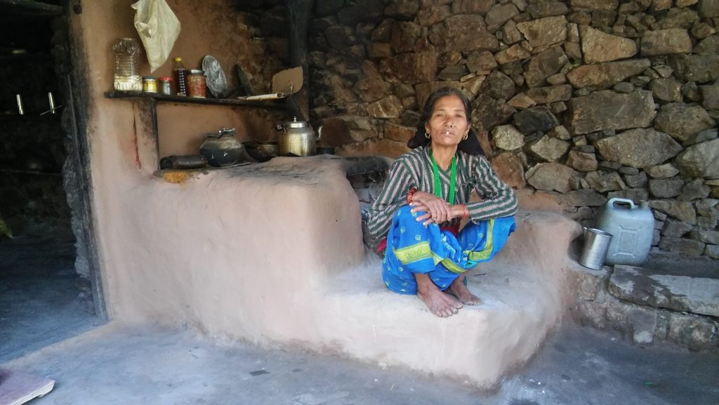 Local village woman posing in front of her outdoor kitchen area.