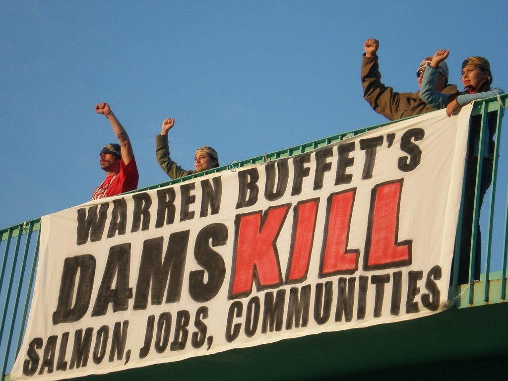 """Four individuals protesting on an bridge in front of a sign reading """"Warren Buffet's dams kill salmon, jobs, communities""""."""