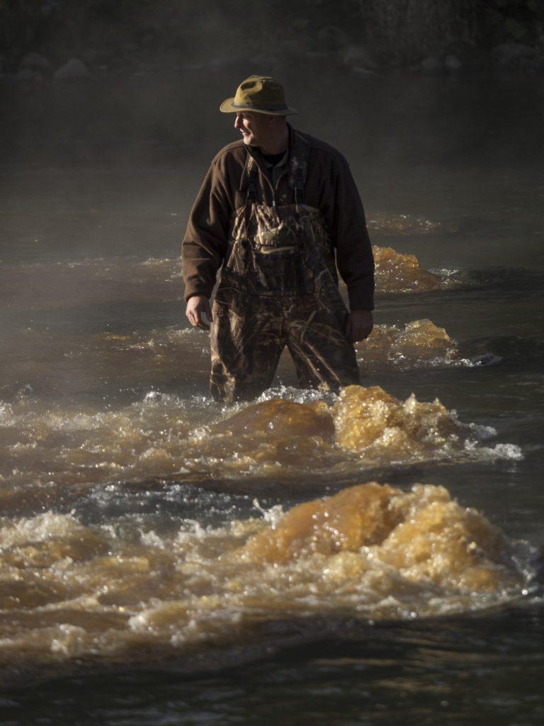 Un homme debout dans une pêche en rivière.