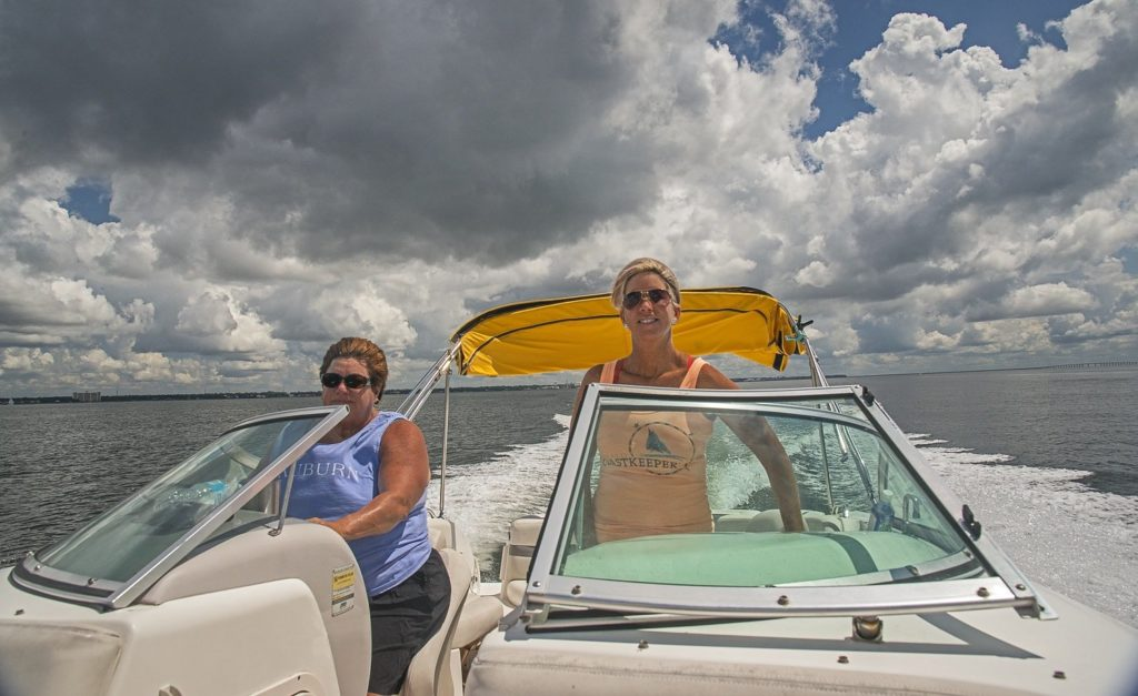 Laurie Murphy and Boardmember Sue Tadaro driving a speed boat in the ocean.