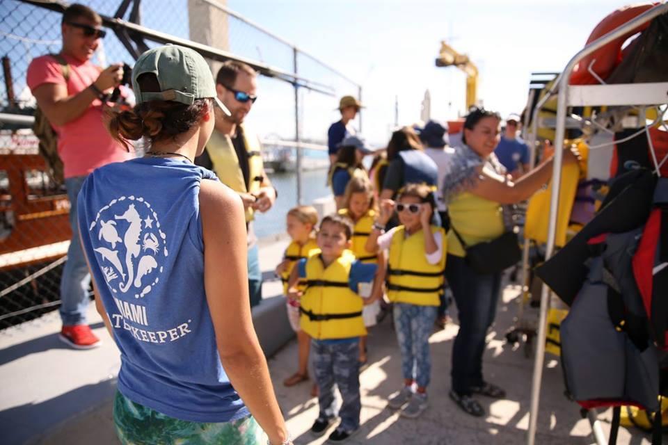 Une femme parle à un groupe d'enfants qui portent tous des gilets de sauvetage.