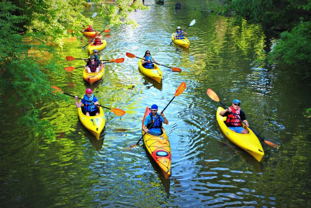 Multiple people kayaking down a river.
