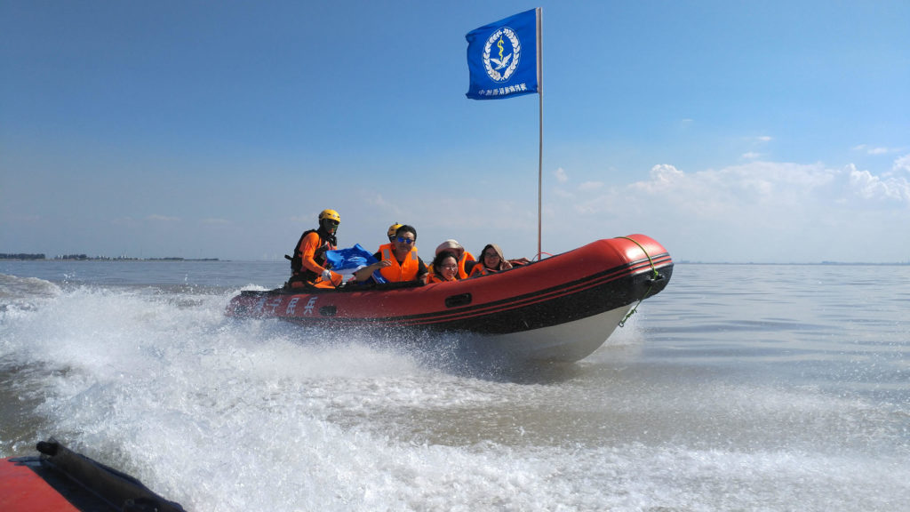 Multiple people riding in a raft boat.