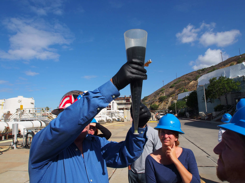 David Huntamer, senior operations supervisor at the Point Loma Wastewater Treatment Plant, shows touring San Diego Coastkeeper staff a sample of San Diego's wastewater before the plant performs primary treatment.