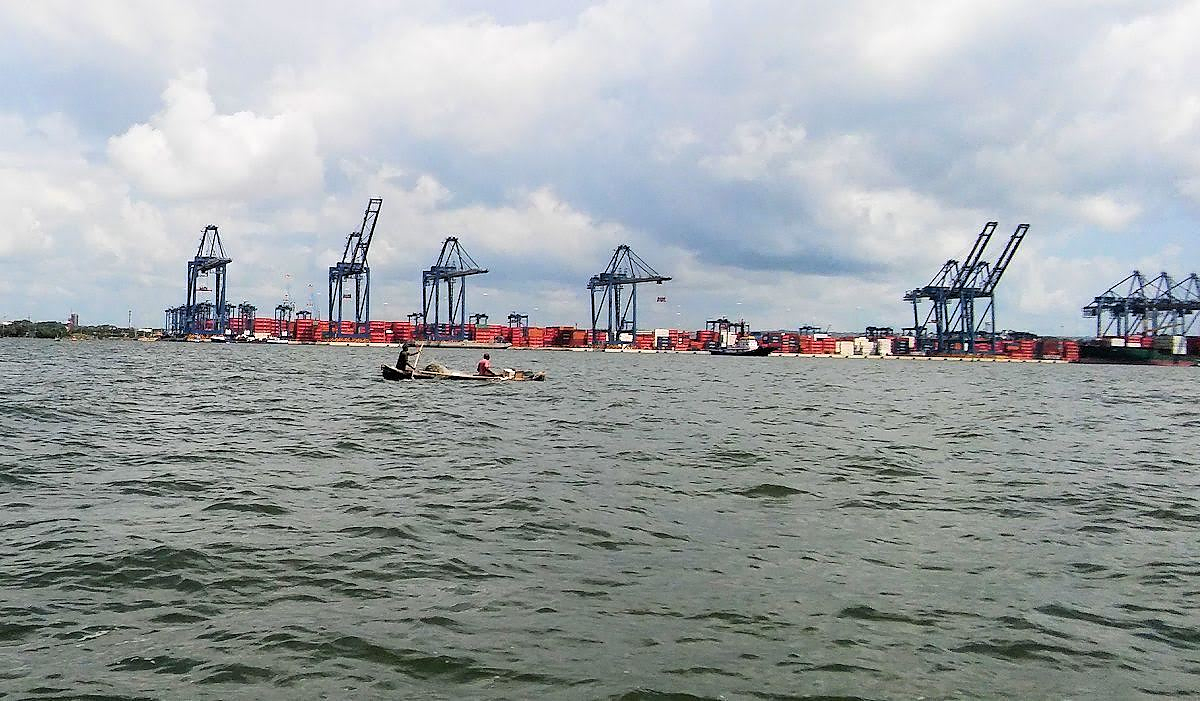 Local fishermen in dugout canoes with makeshift paddles fish in the bay amidst the enormous industrial container port.