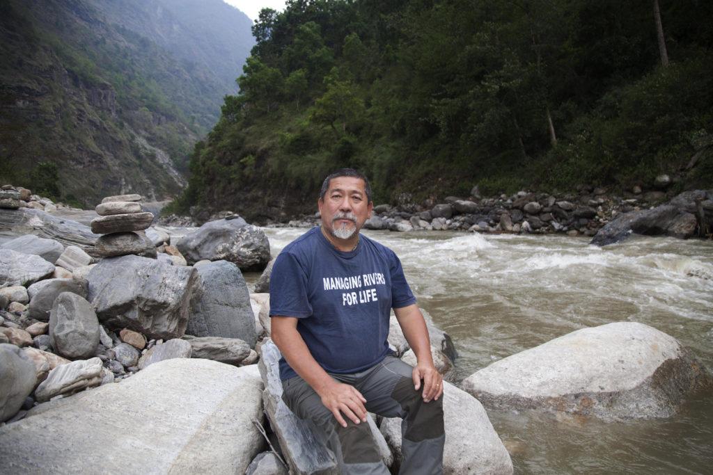 Karnali River Waterkeeper Megh Ale sitting on rocks on the edge of the Karnali.