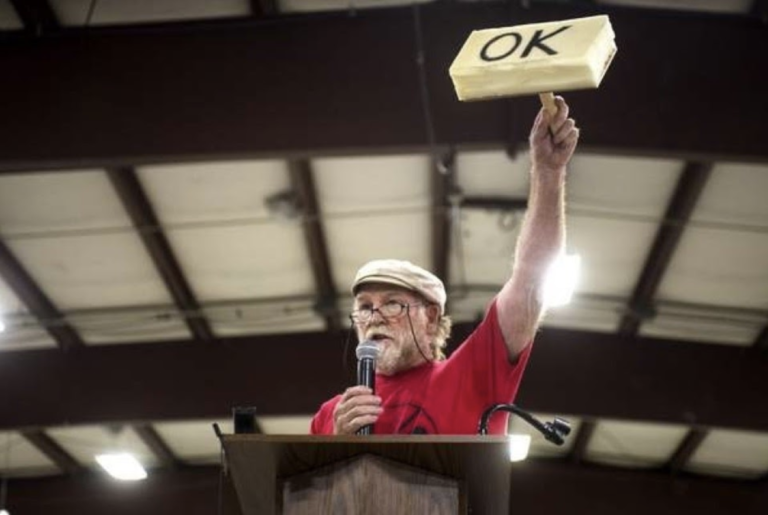 Opponent of LNG in Oregon holds up home-made rubberstamp during FERC hearing in 2016.