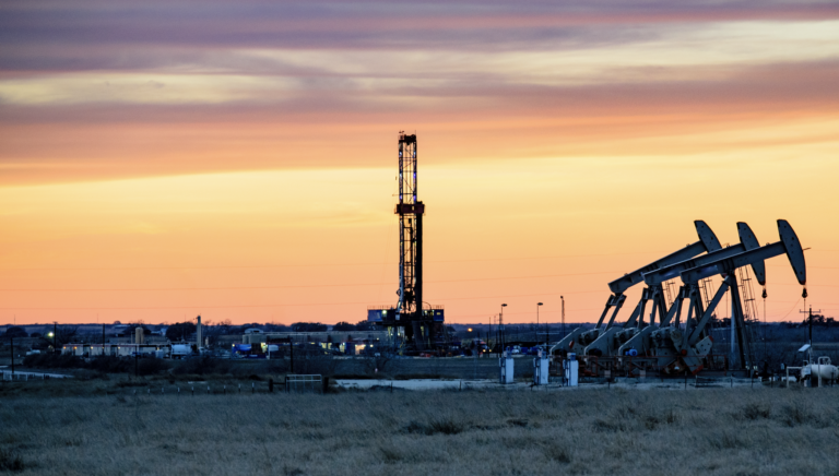 A gas drilling rig for fracking with a sunset in the background.