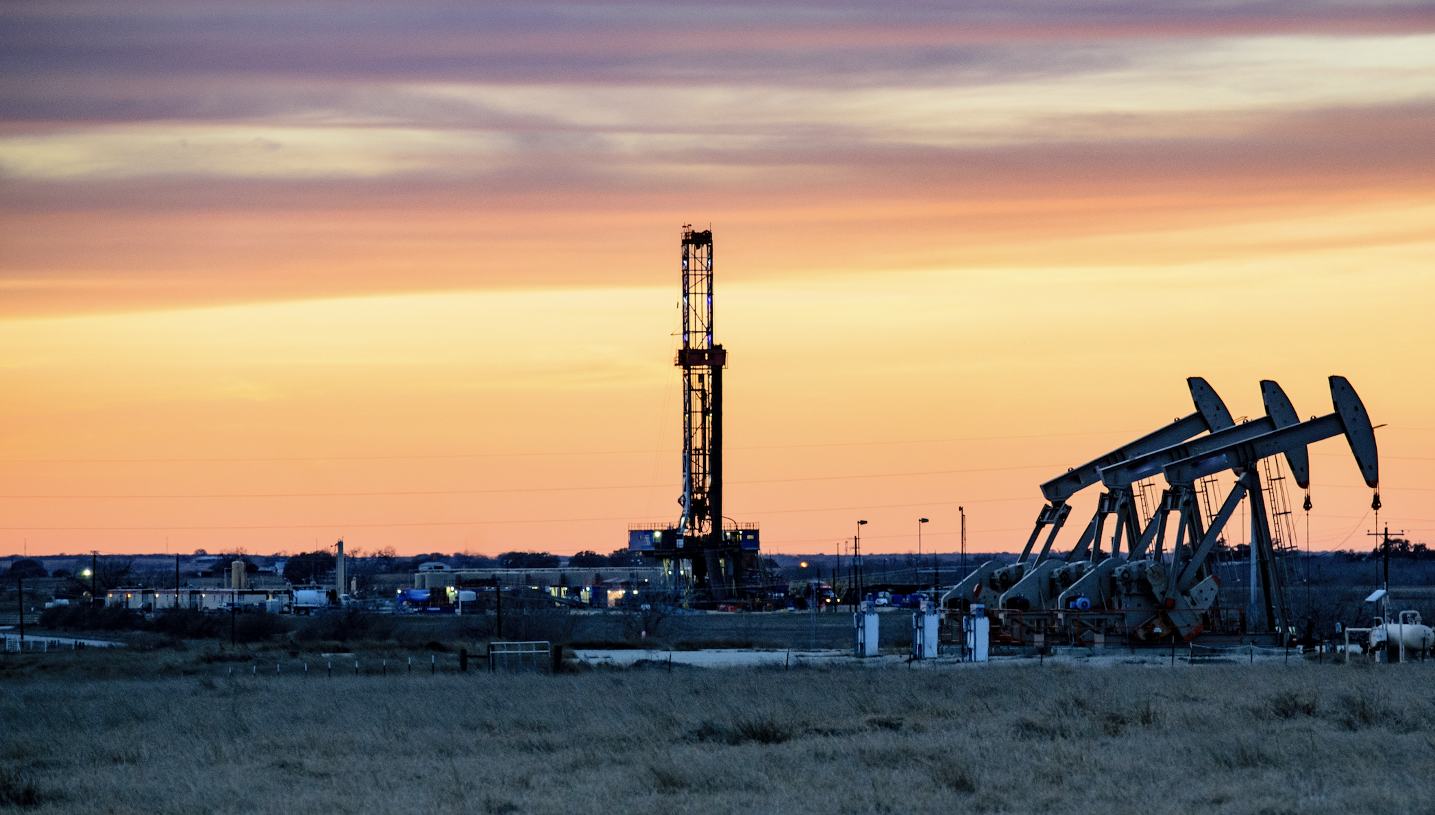 Una plataforma de perforación de gas para fracking con una puesta de sol de fondo.