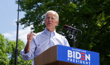Joe Biden standing behind a podium at an outdoor event with green trees in the background.