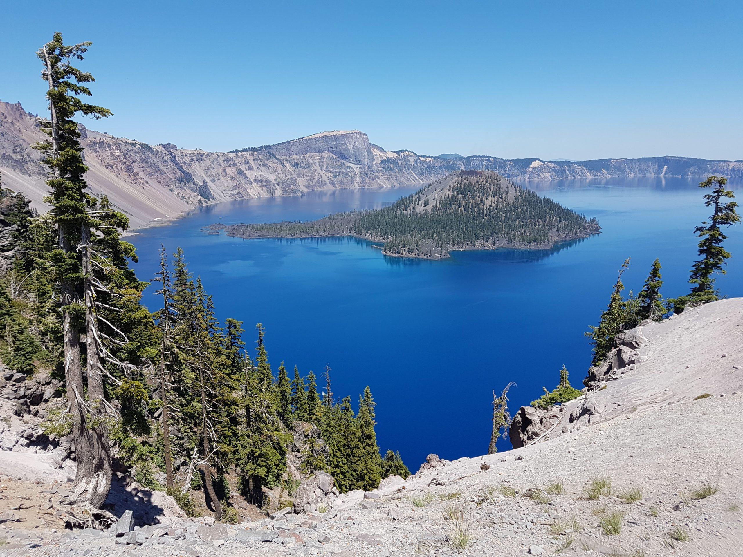 有一个海岛在它和树中间的一个大蓝色湖在前景。