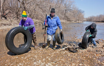 Three people roll large tires away from a riverbank.