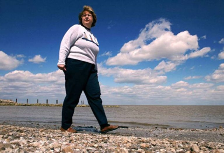 Sandy Bihn walks on a rocky beach near the water.