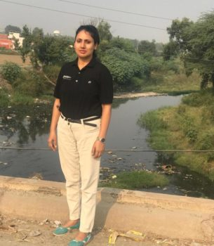 The East Kali River Waterkeeper, Sonal Bhushan, stands next to a river with green trees along the riverbanks.