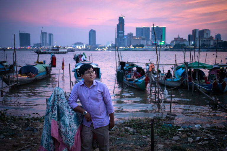 Senglong Youk, Waterkeeper of the Mekong and Tonle Sap poses for a photo in front of a Cham muslim fishing community in Chrouy Changvar, a peninsula between both rivers on the outskirts of Phnom Penh. Phnom Penh, Cambodia.