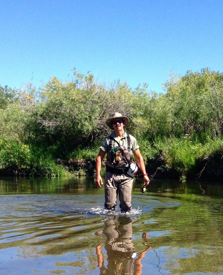 Alto Missouri Waterkeeper Guy Alsentzer se encuentra en el agua hasta las rodillas en un río con árboles al fondo.