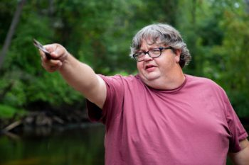 Jeff Currie the Lumber Riverkeeper is pointing his finger. He is wearing a red shirt and there are green trees behind him.